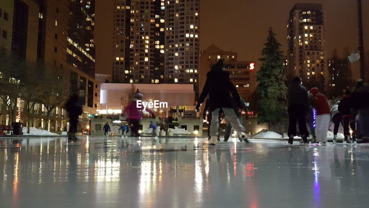 city, architecture, night, built structure, building exterior, illuminated, modern, real people, skyscraper, ice-skating, lifestyles, cityscape, ice rink, outdoors