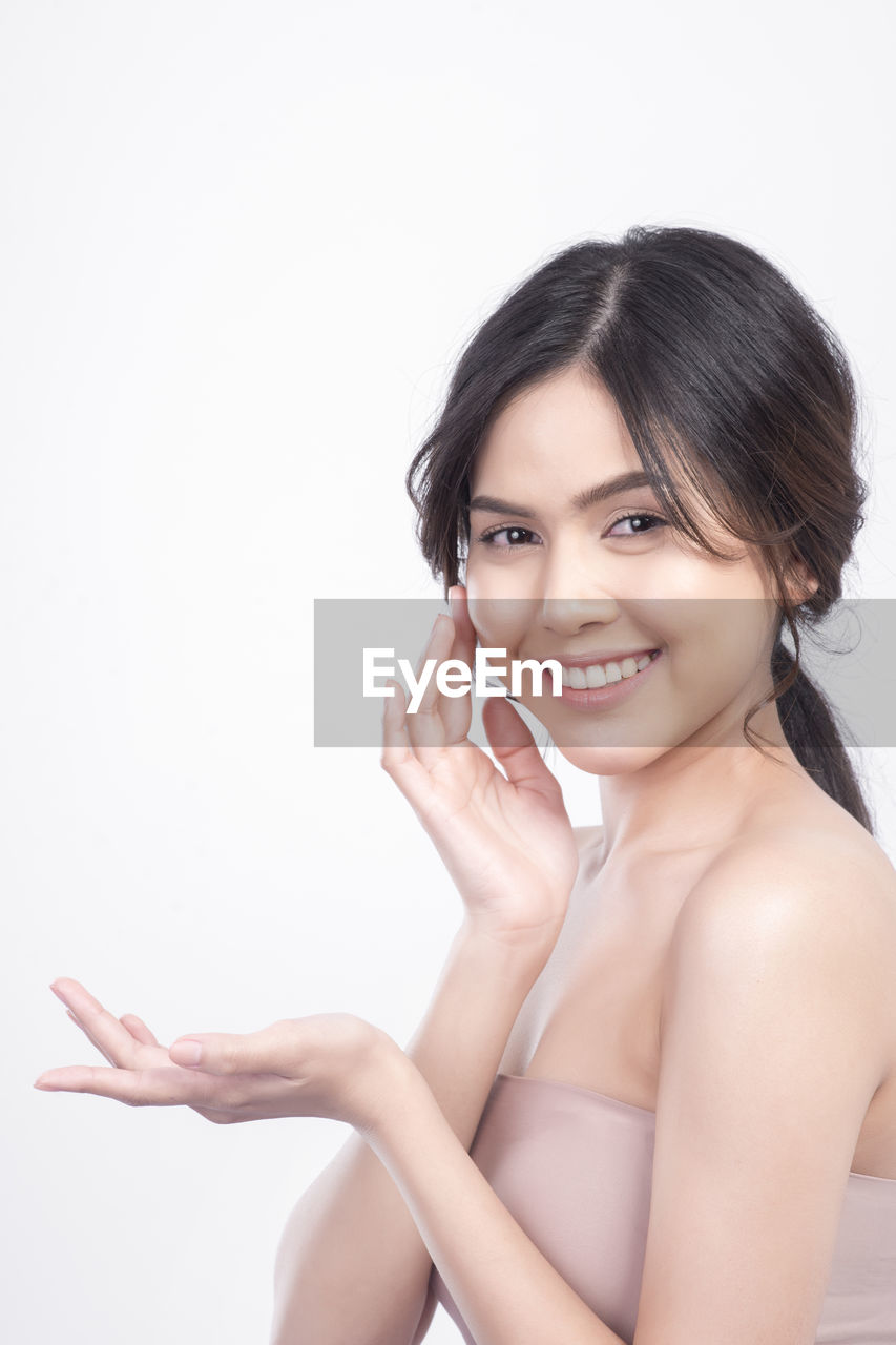 Portrait of smiling beautiful woman applying cream on cheek against white background