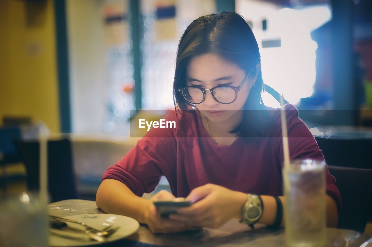 Woman Using Phone While Sitting At Table In Restaurant