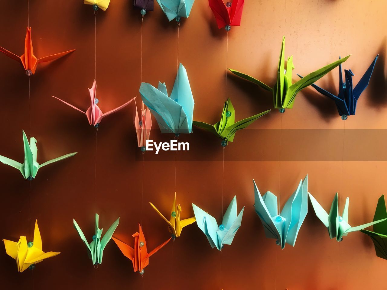Colorful paper cranes hanging against wall
