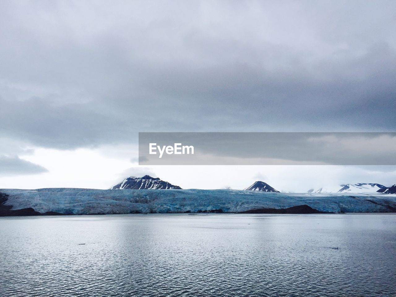 mountain, beauty in nature, scenics, tranquil scene, nature, tranquility, cold temperature, lake, waterfront, outdoors, weather, winter, idyllic, remote, mountain range, water, snow, no people, sky, ice, glacier, cloud - sky, frozen, day, snowcapped mountain, landscape, iceberg