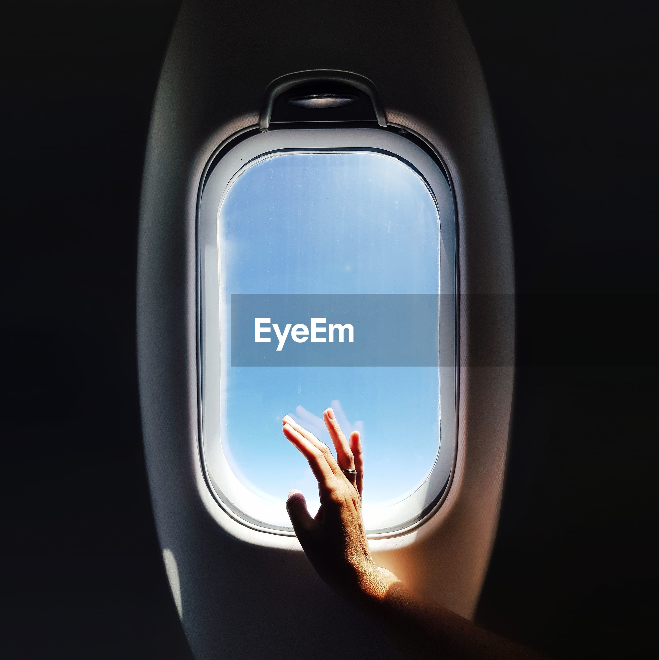 Cropped hand of woman touching airplane window
