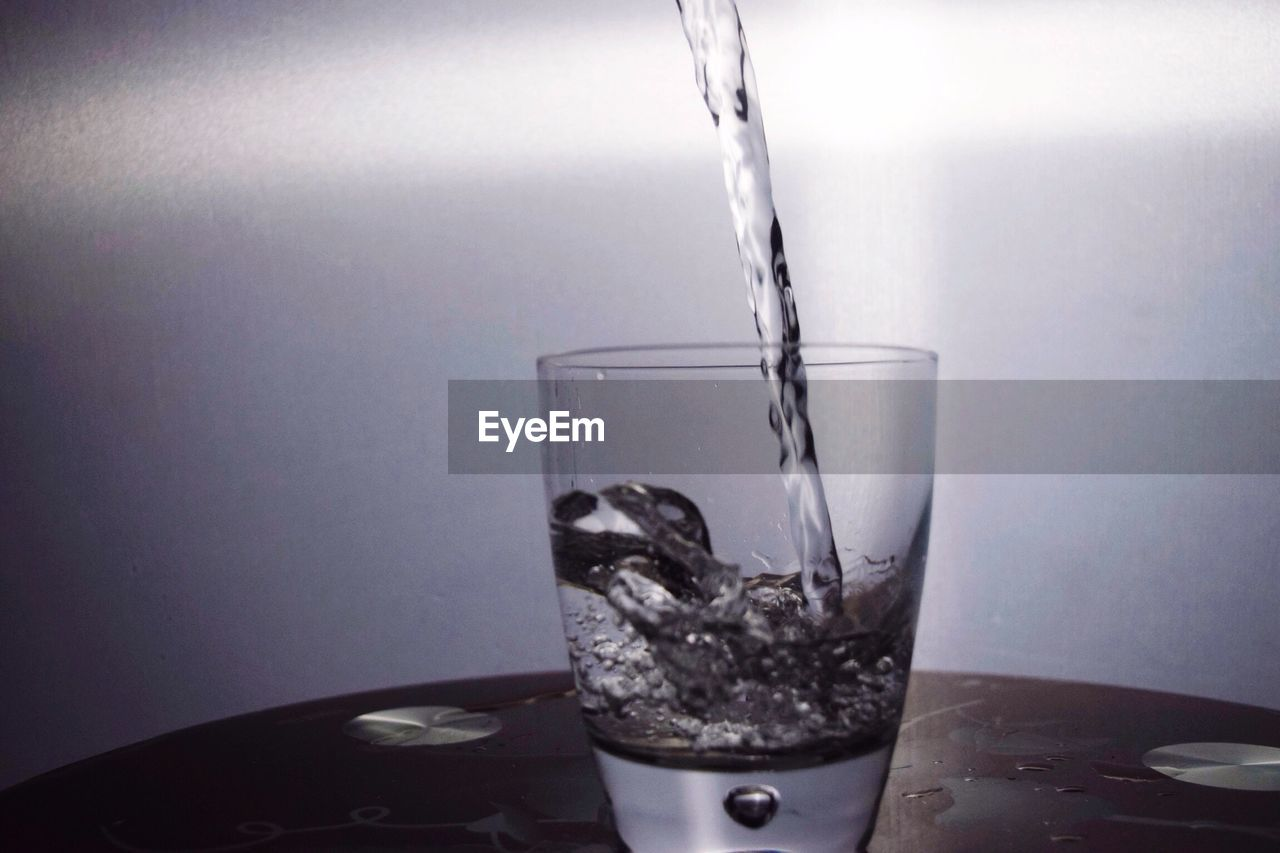 refreshment, drink, drinking glass, motion, drinking water, freshness, indoors, water, no people, food and drink, table, liquid, close-up, dissolving, day