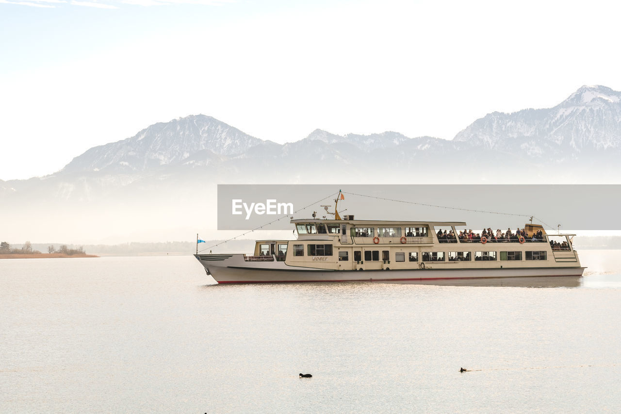 mountain, nautical vessel, transportation, mode of transportation, sky, water, scenics - nature, beauty in nature, mountain range, waterfront, nature, sea, tranquil scene, day, no people, travel, tranquility, ship, outdoors, passenger craft, snowcapped mountain