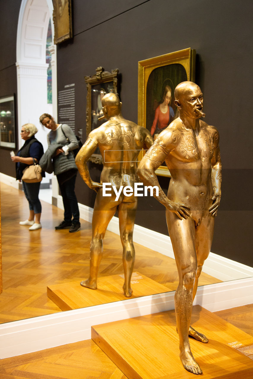 sculpture, art and craft, statue, representation, indoors, museum, architecture, craft, human representation, male likeness, group of people, creativity, hardwood floor, full length, built structure, art museum, men, flooring, arts culture and entertainment, people