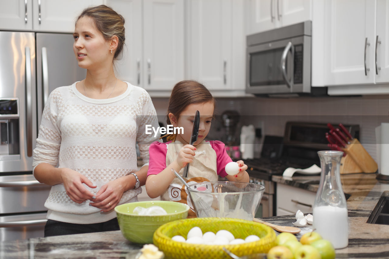 Cute Girl With Mother Preparing Food In Kitchen