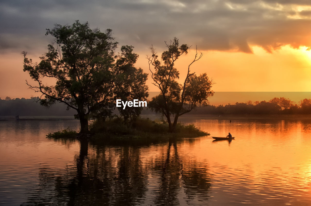 water, sunset, sky, tree, beauty in nature, lake, plant, scenics - nature, cloud - sky, orange color, waterfront, tranquility, reflection, tranquil scene, silhouette, nature, nautical vessel, transportation, non-urban scene, outdoors
