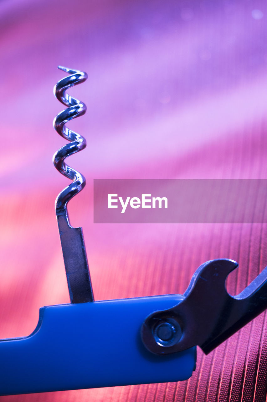 no people, metal, close-up, focus on foreground, corkscrew, indoors, pink color, spiral, sharp, blue, pattern, still life, work tool, single object, table, household equipment, equipment, nature, wood - material