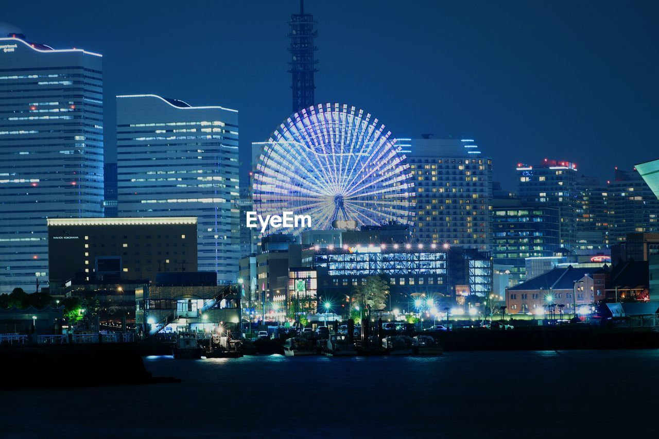 night, illuminated, building exterior, architecture, waterfront, built structure, city, cityscape, skyscraper, ferris wheel, no people, outdoors, arts culture and entertainment, sky, clear sky, water, urban skyline