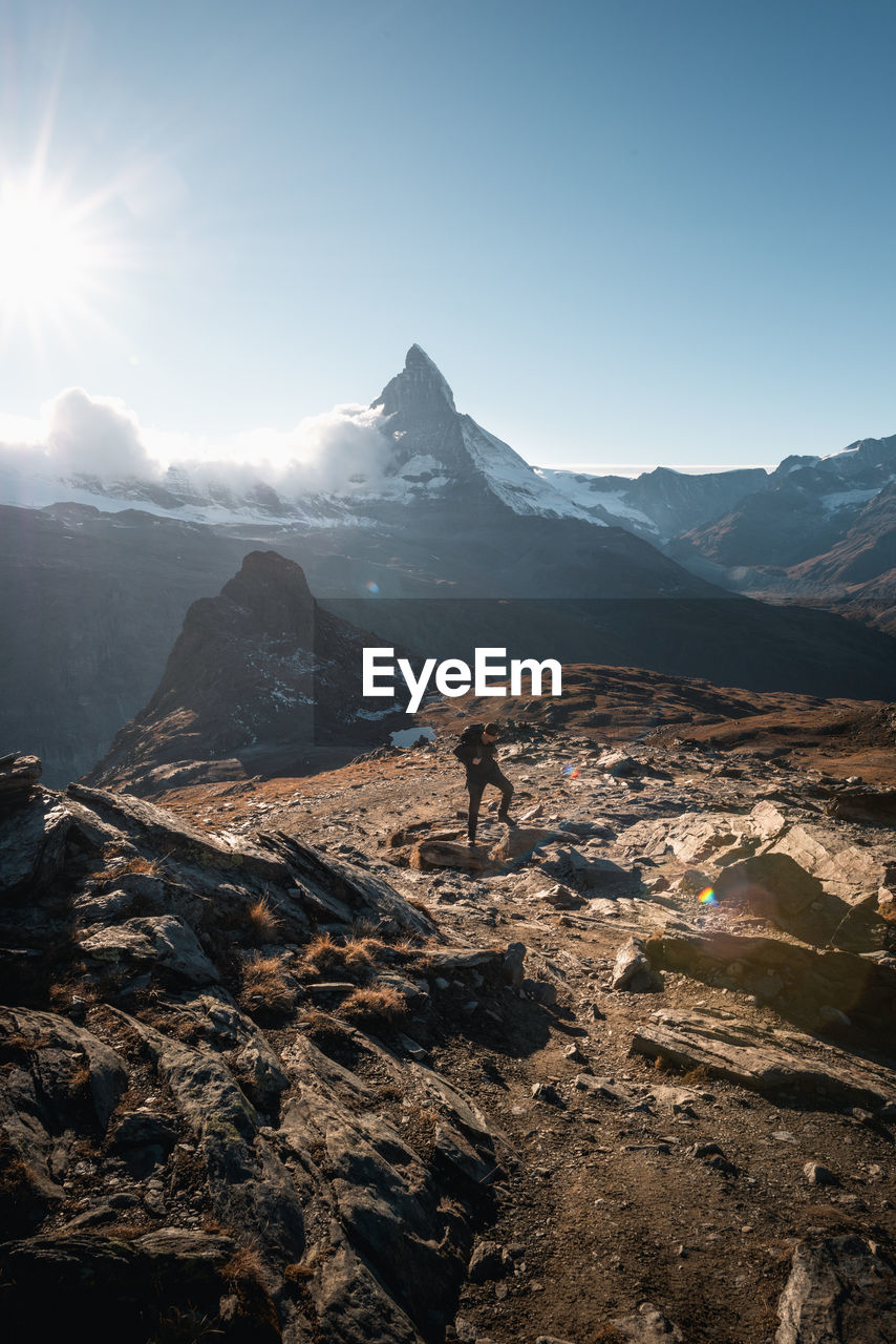 Scenic view of mountains with man standing on rocks against sky