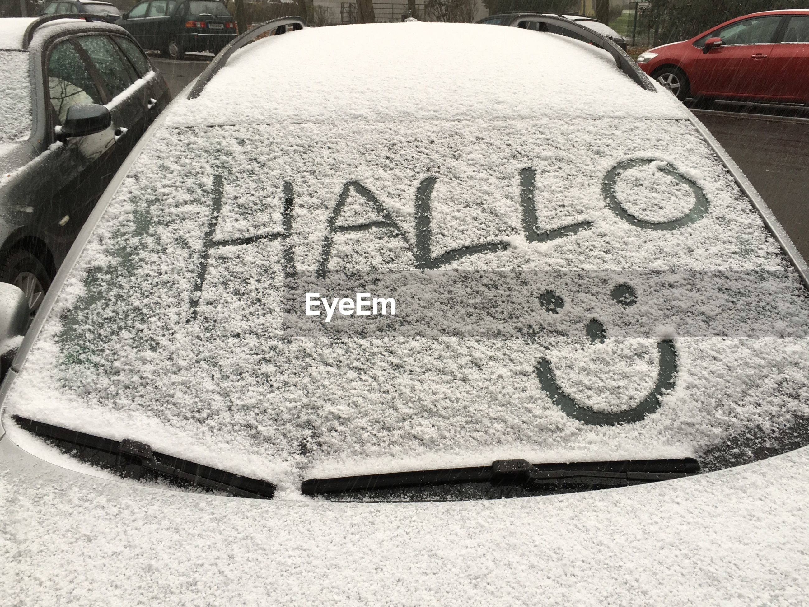 High angle view of text on snow covered car windshield