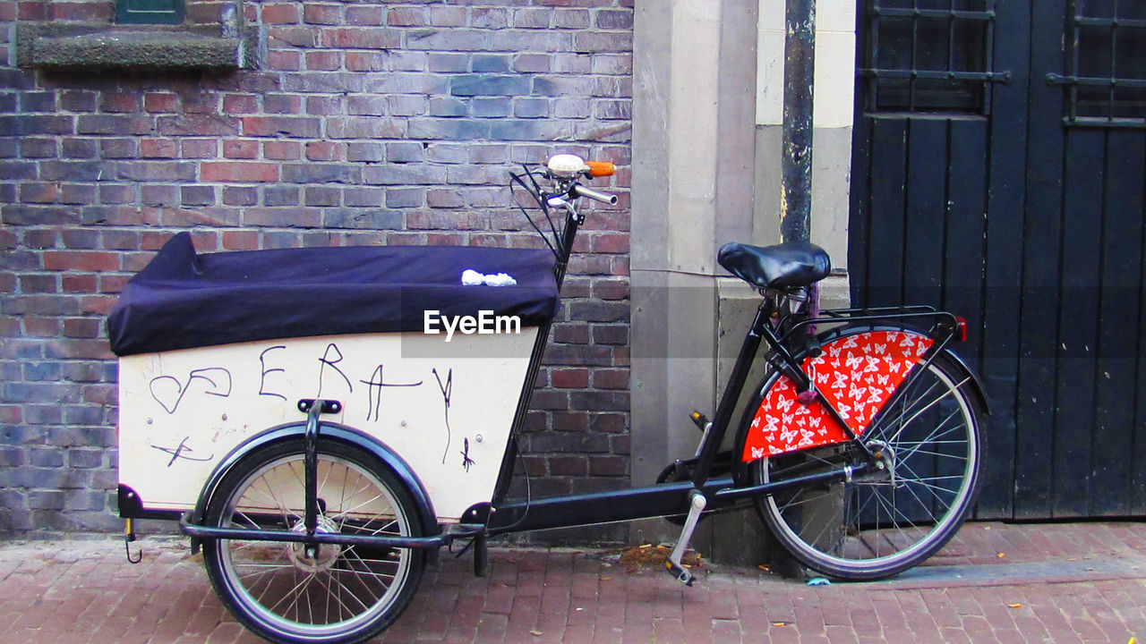 bicycle, transportation, land vehicle, mode of transport, stationary, bicycle basket, brick wall, outdoors, no people, architecture, built structure, building exterior, day, scooter, red, bicycle rack, city
