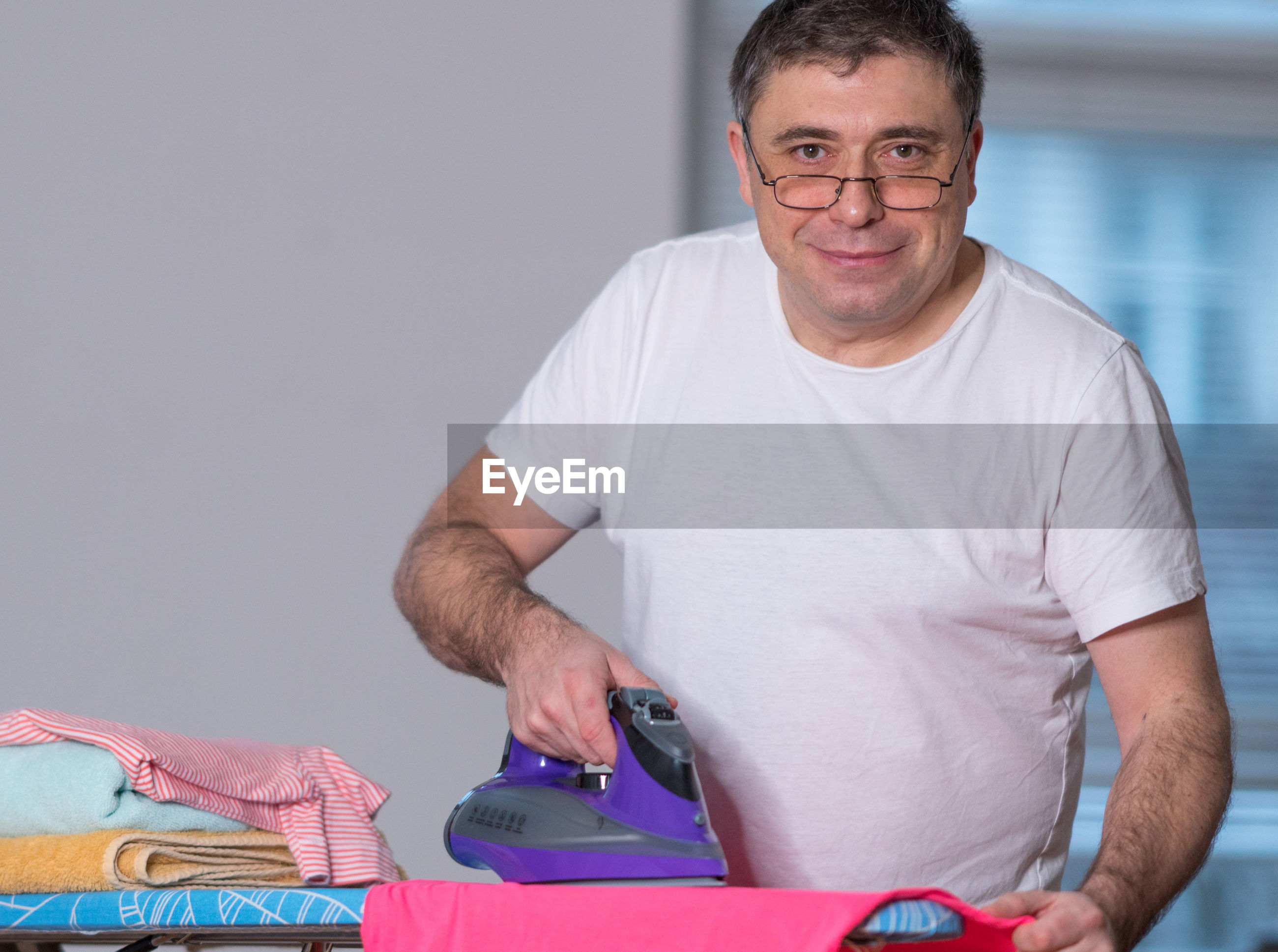 Portrait of man ironing cloth at home
