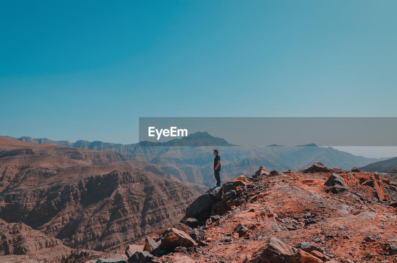 Full Length Of Man Standing On Rocky Mountain Against Sky