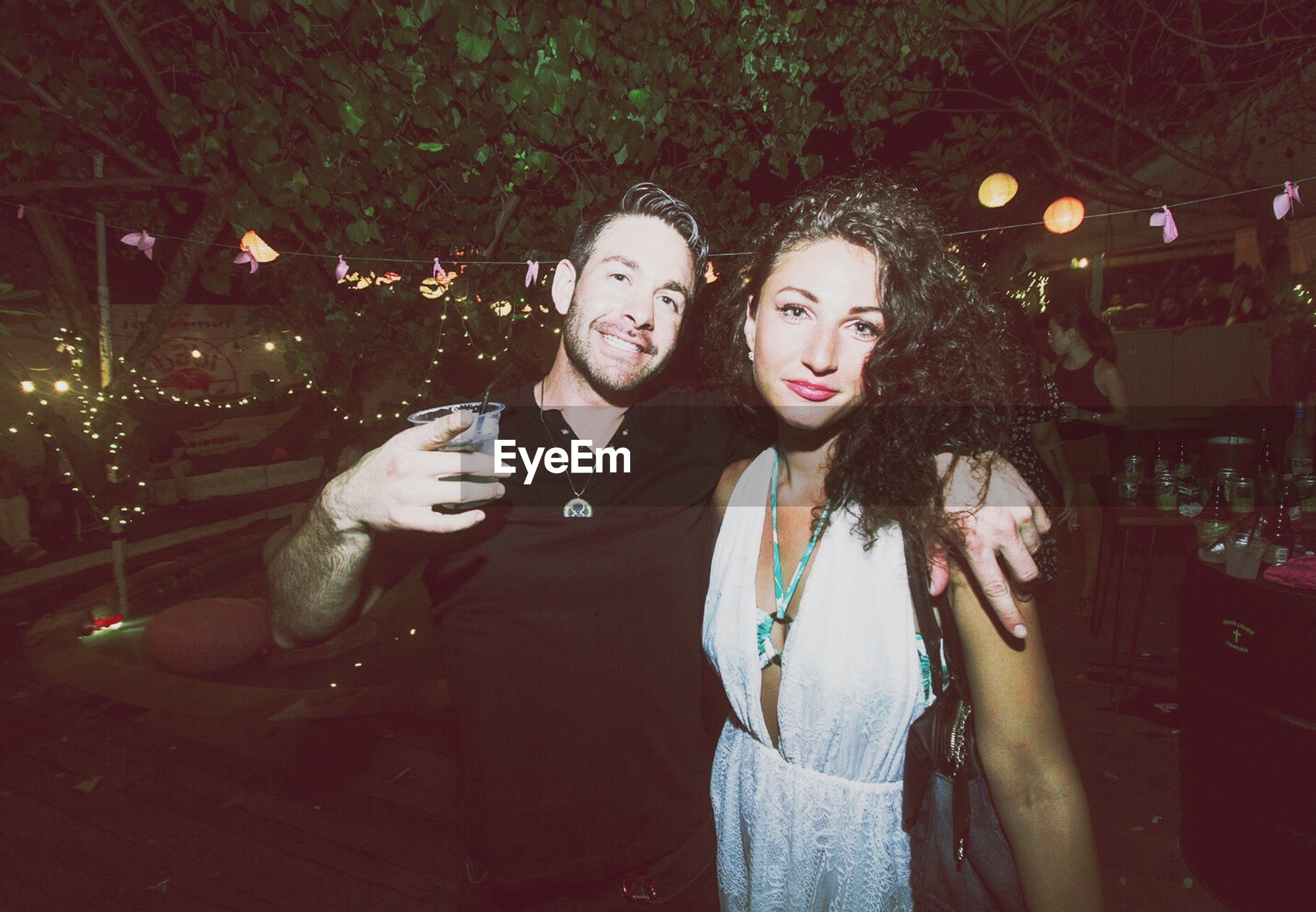 two people, looking at camera, young adult, portrait, young men, young women, adults only, waist up, party - social event, night, adult, nightlife, holding, people, togetherness, front view, celebration, friendship, men, outdoors, antler