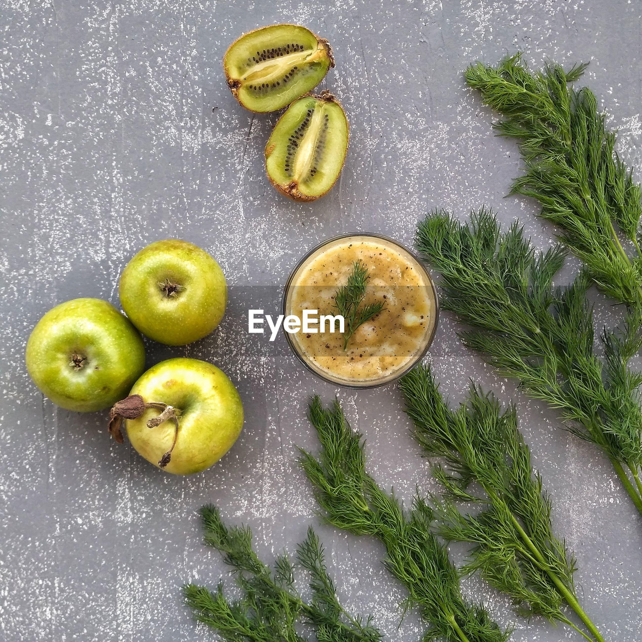 High angle view of juice with fruits and dill on table