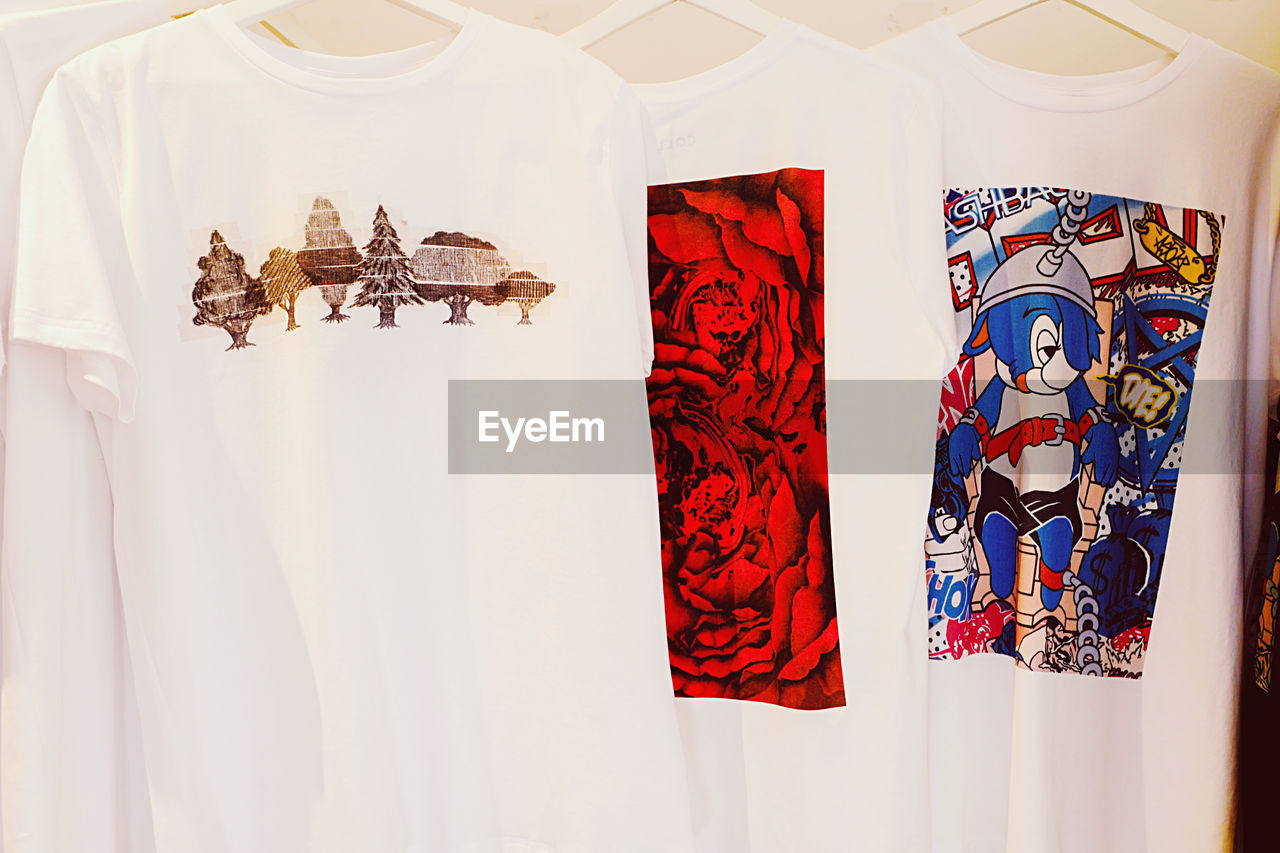 no people, indoors, representation, white color, pattern, variation, creativity, still life, multi colored, textile, human representation, choice, clothing, art and craft, hanging, side by side, retail, for sale, red, female likeness, floral pattern, retail display, consumerism
