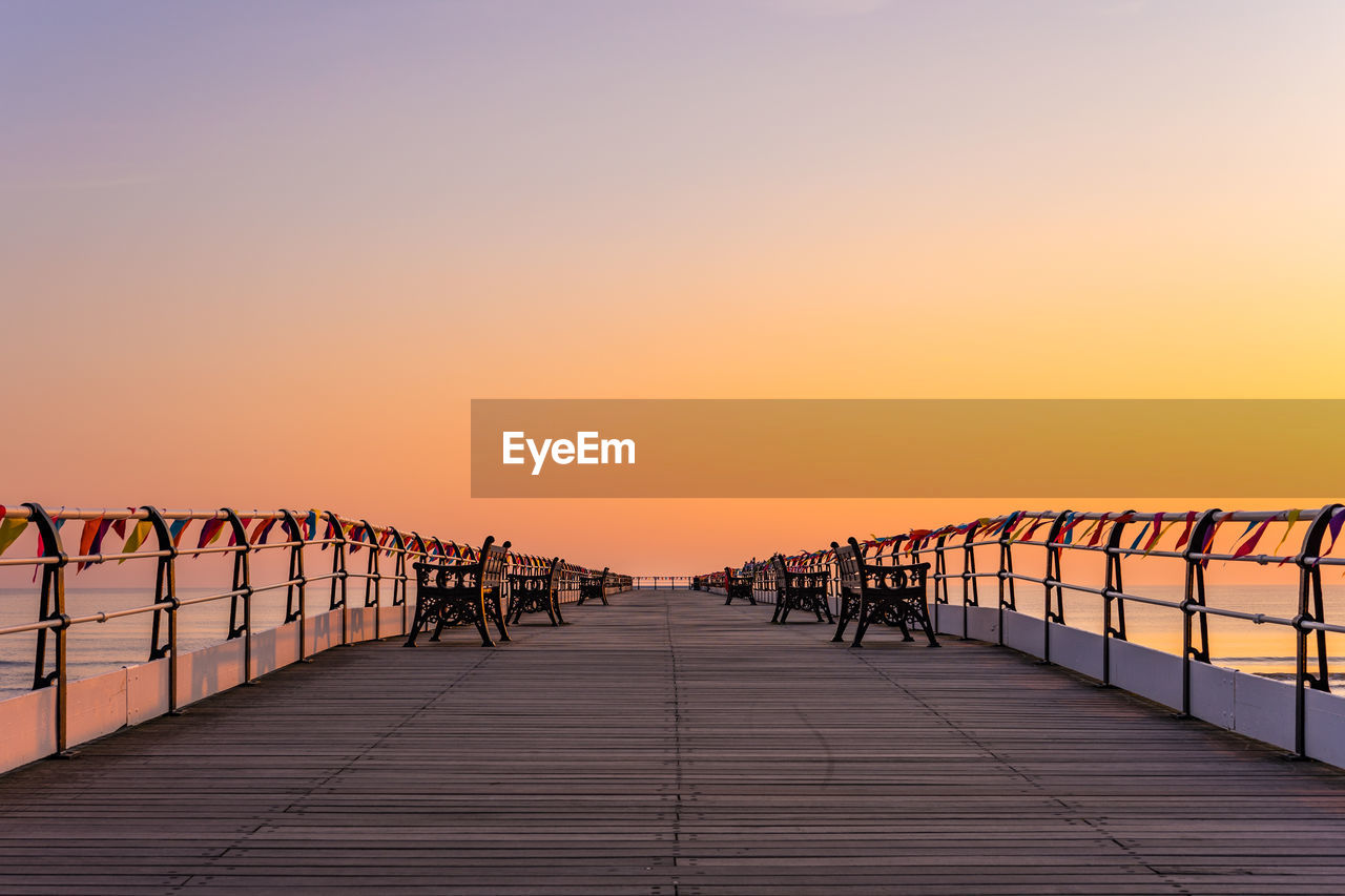 sunset, sky, orange color, the way forward, clear sky, copy space, direction, nature, diminishing perspective, railing, beauty in nature, in a row, outdoors, real people, scenics - nature, water, built structure, connection, architecture, tranquil scene
