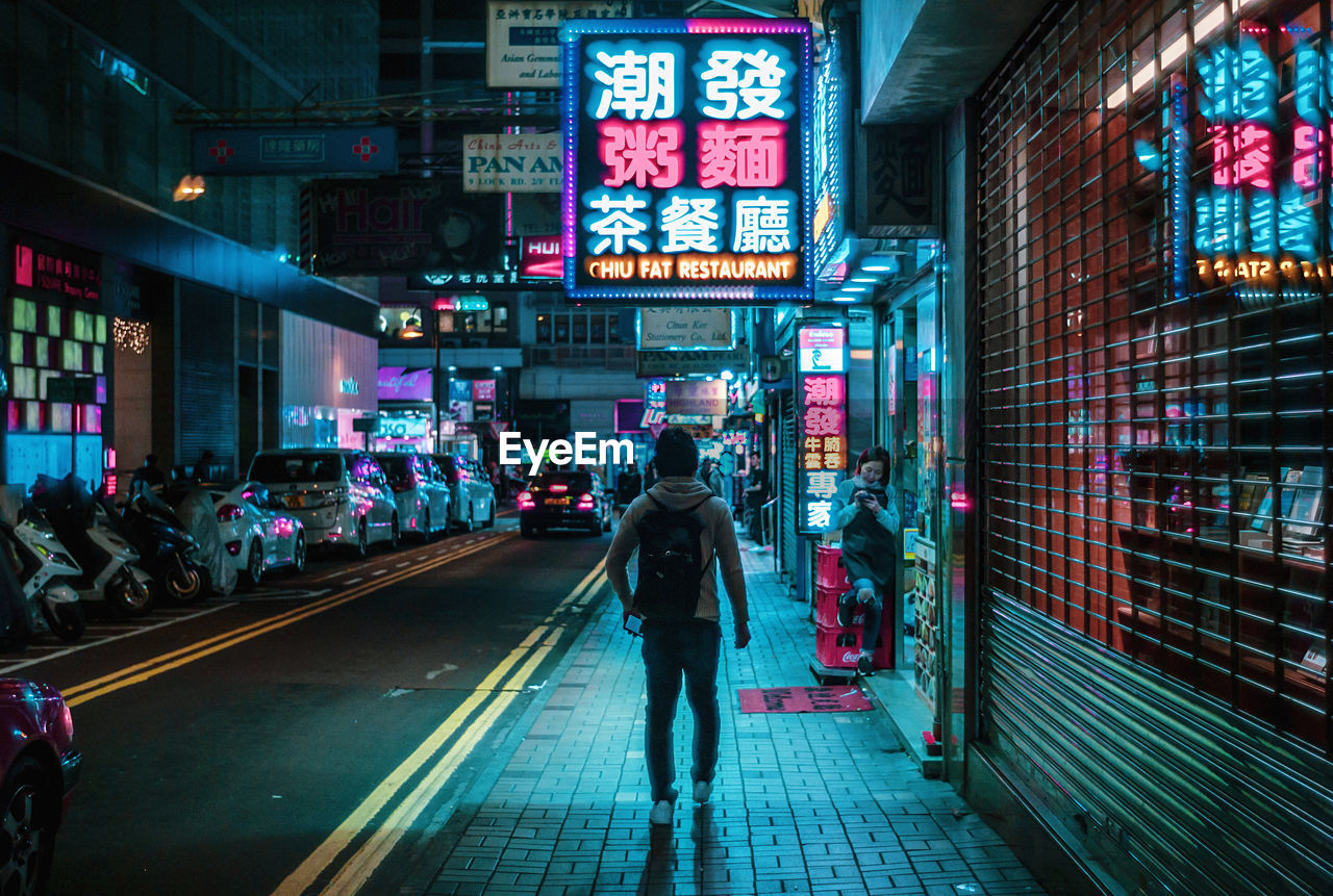 city, illuminated, architecture, real people, building exterior, built structure, street, transportation, lifestyles, night, city life, people, men, walking, communication, rear view, full length, sign