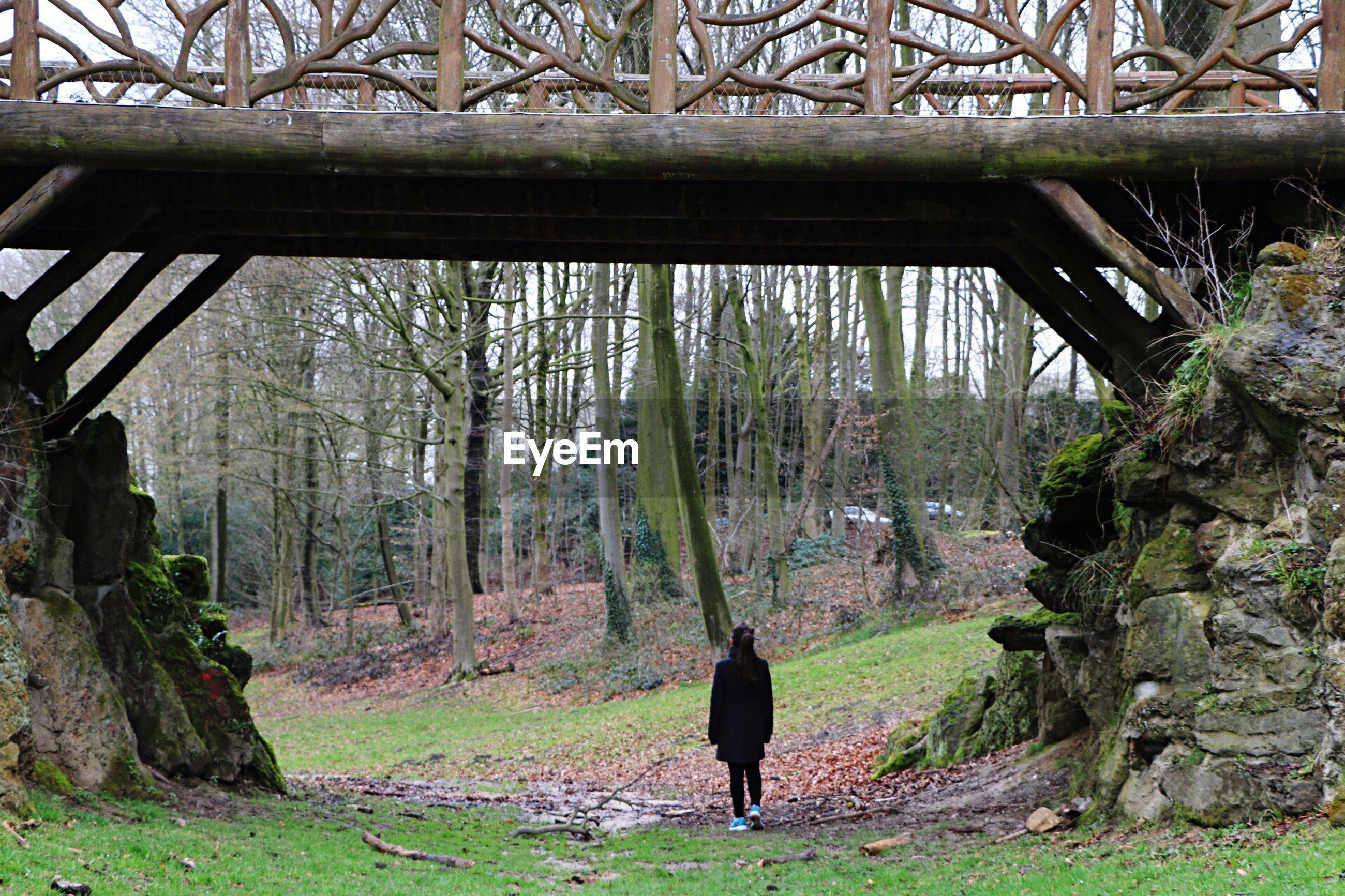 Woman standing below wooden bridge in forest