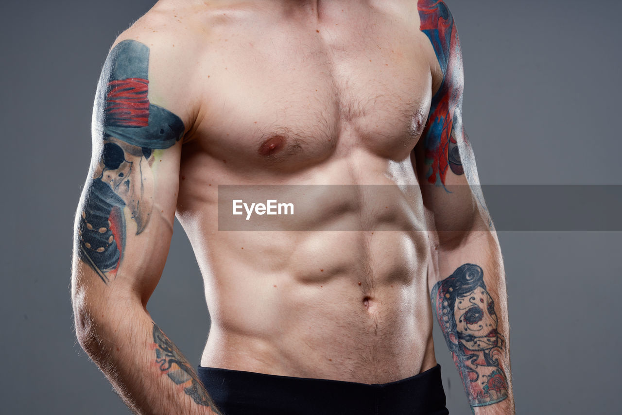 MIDSECTION OF SHIRTLESS MAN WITH TATTOO ON BED