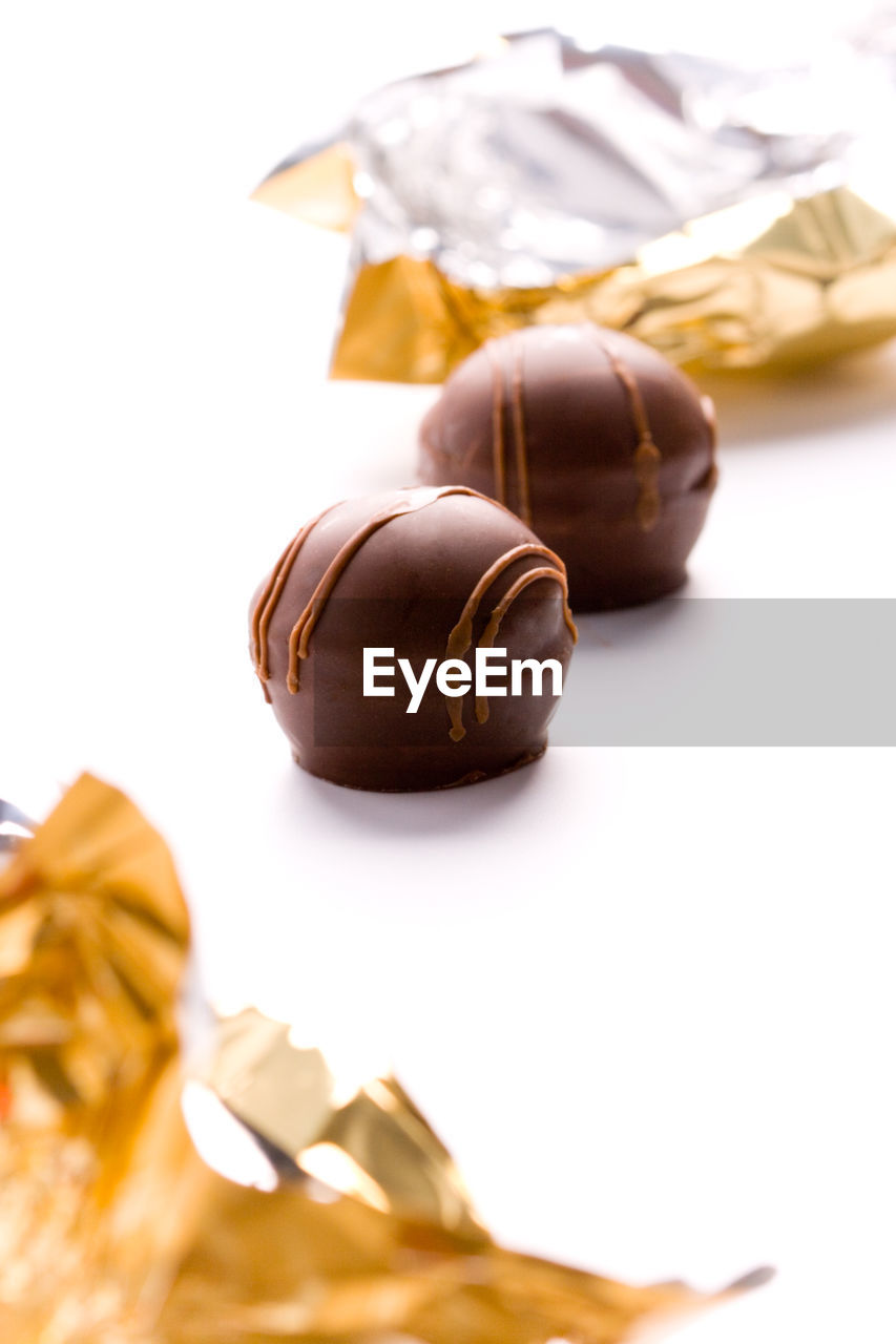 food, still life, food and drink, close-up, no people, indoors, white background, studio shot, brown, freshness, chocolate, table, sweet food, indulgence, unhealthy eating, selective focus, sweet, temptation, ready-to-eat, snack