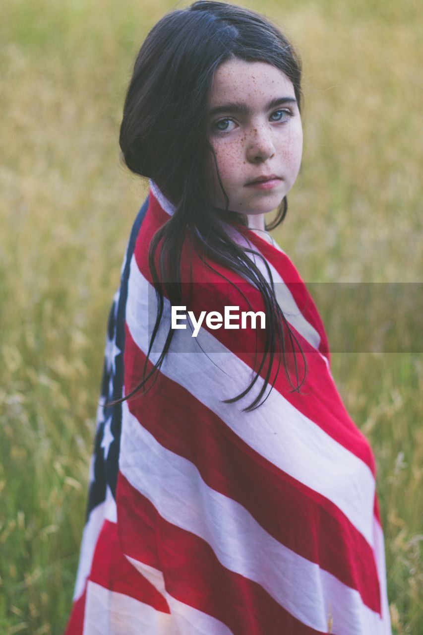 Portrait Of Girl Wrapped In American Flag While Standing On Field