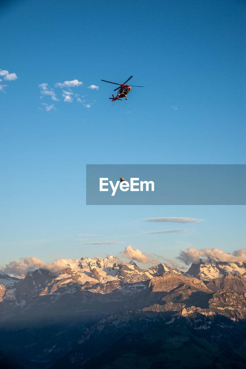 Helicopter Flying Over Landscape Against Sky