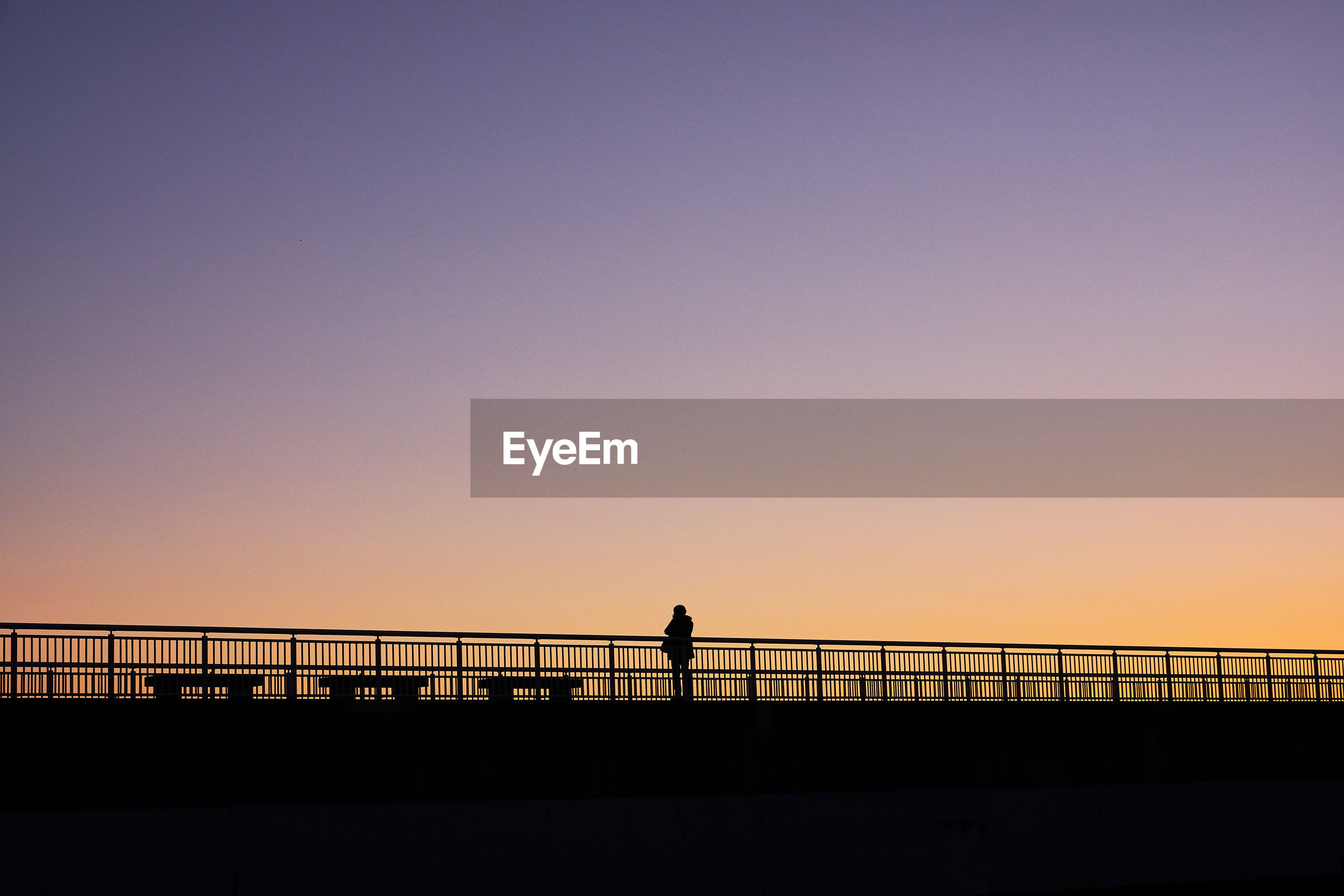 Silhouette man standing on bridge against clear sky during sunset