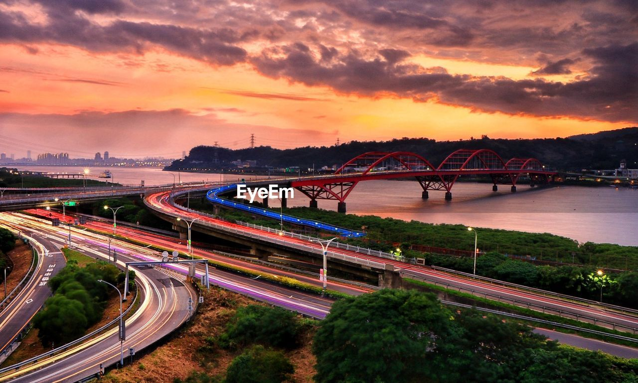 transportation, sunset, sky, connection, architecture, bridge, bridge - man made structure, built structure, city, cloud - sky, high angle view, road, nature, light trail, engineering, motion, long exposure, speed, illuminated, outdoors, multiple lane highway