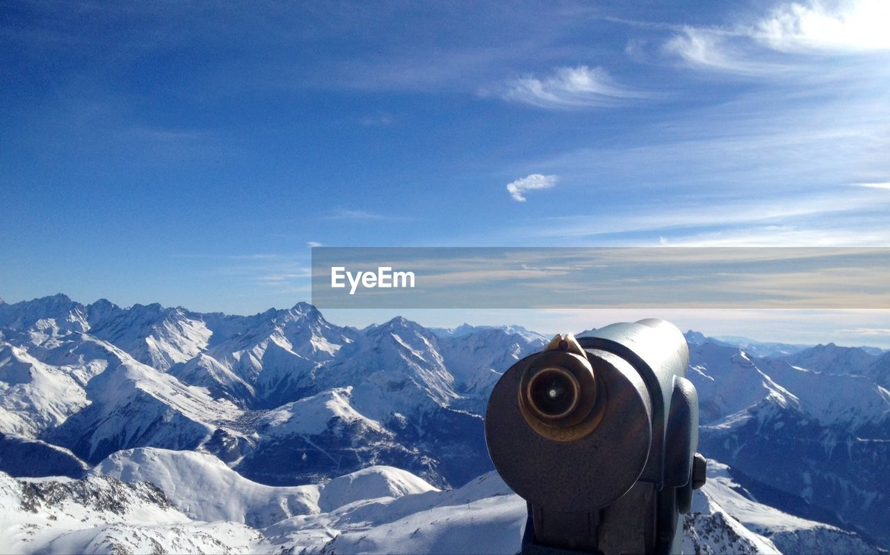 Coin-Operated Binocular Against Snow Covered Mountains
