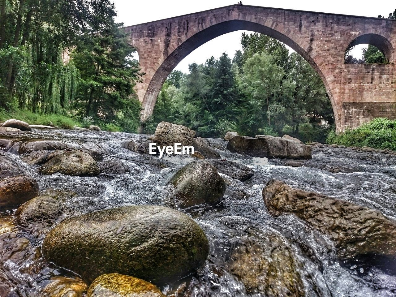 bridge - man made structure, connection, arch, arch bridge, river, water, architecture, built structure, nature, outdoors, no people, tree, day, rock - object, waterfall, beauty in nature, under, sky
