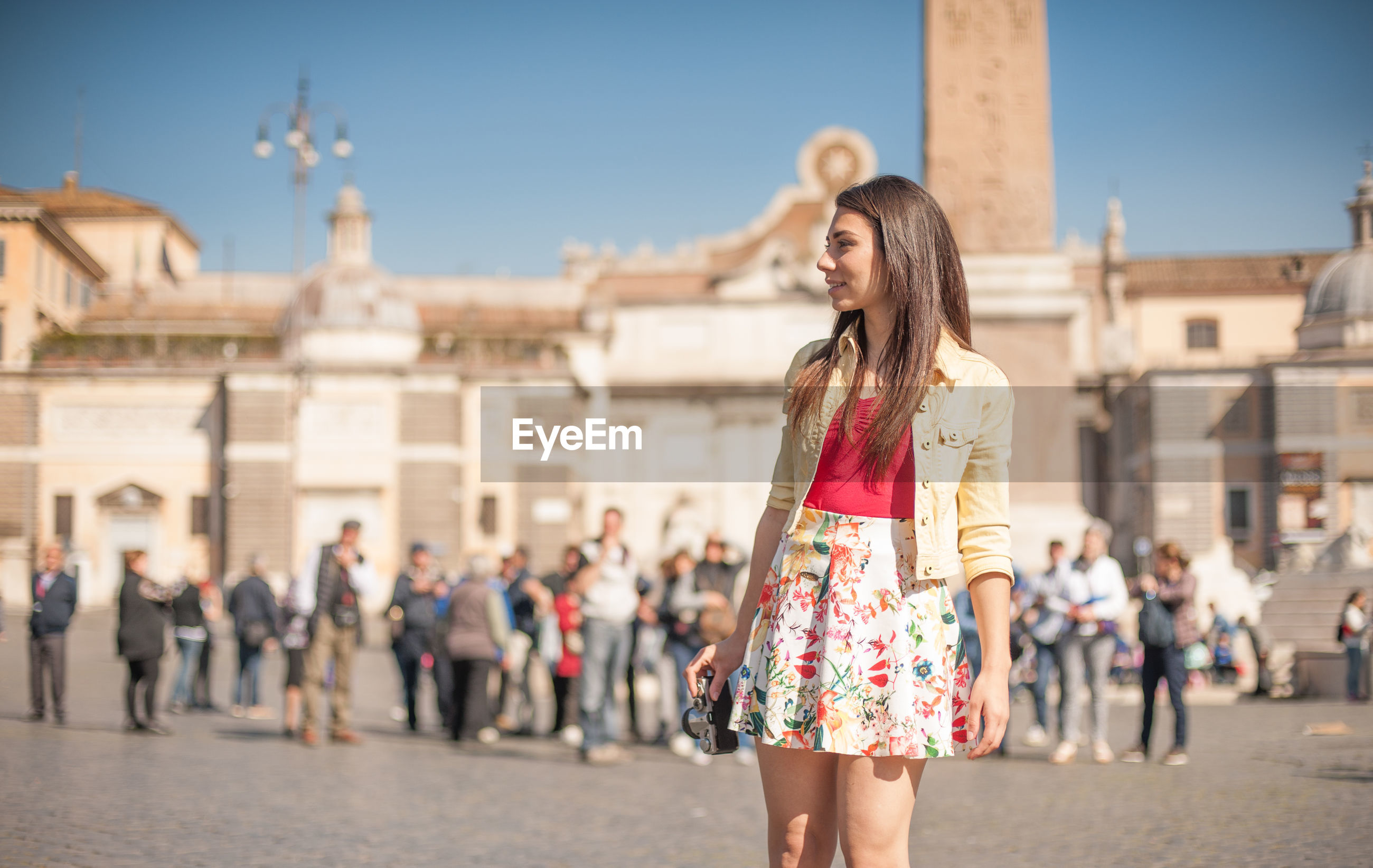 Beautiful woman standing with camera by historic building against sky
