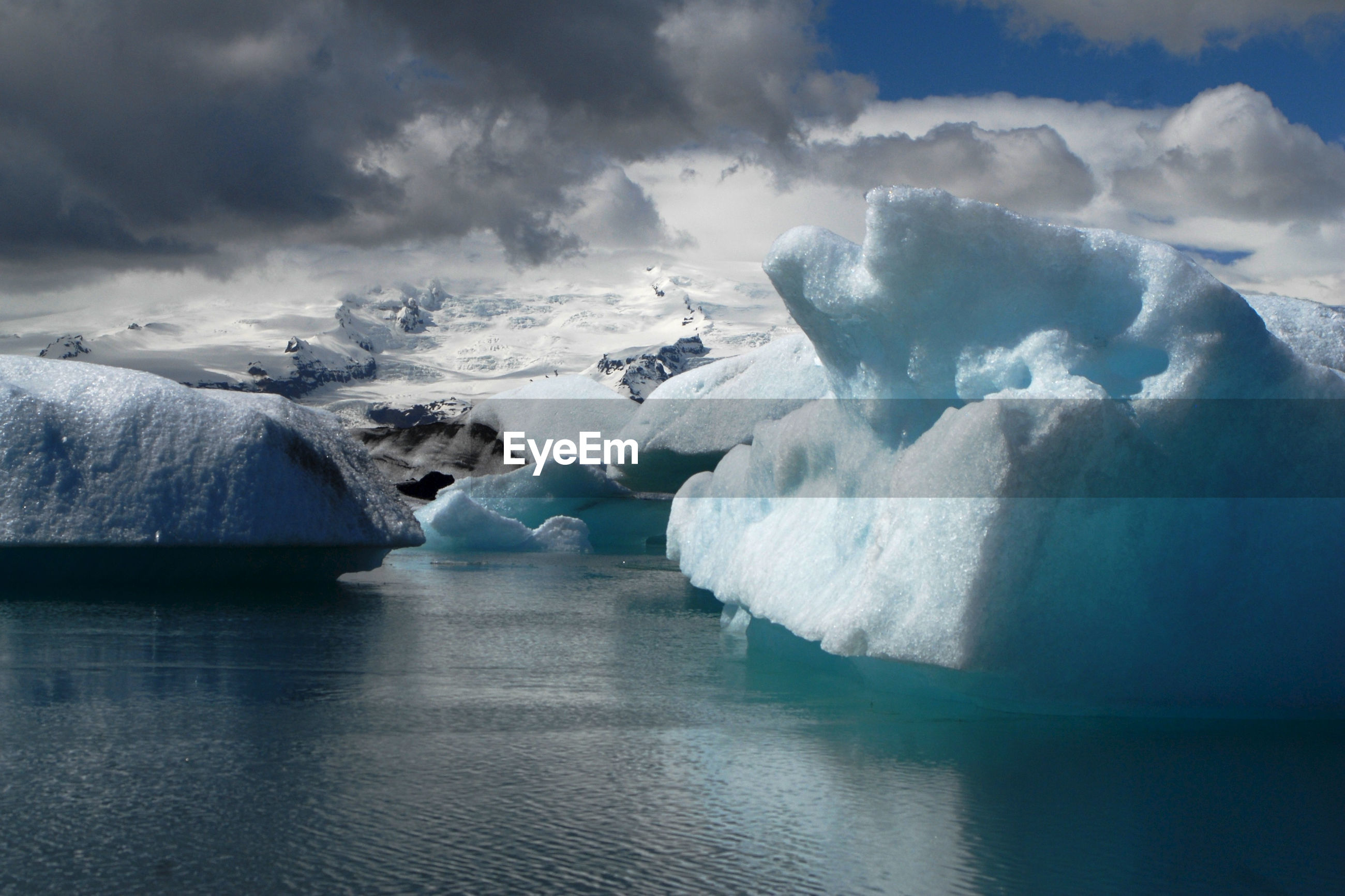 Scenic view of glaciers in lake against cloudy sky during winter