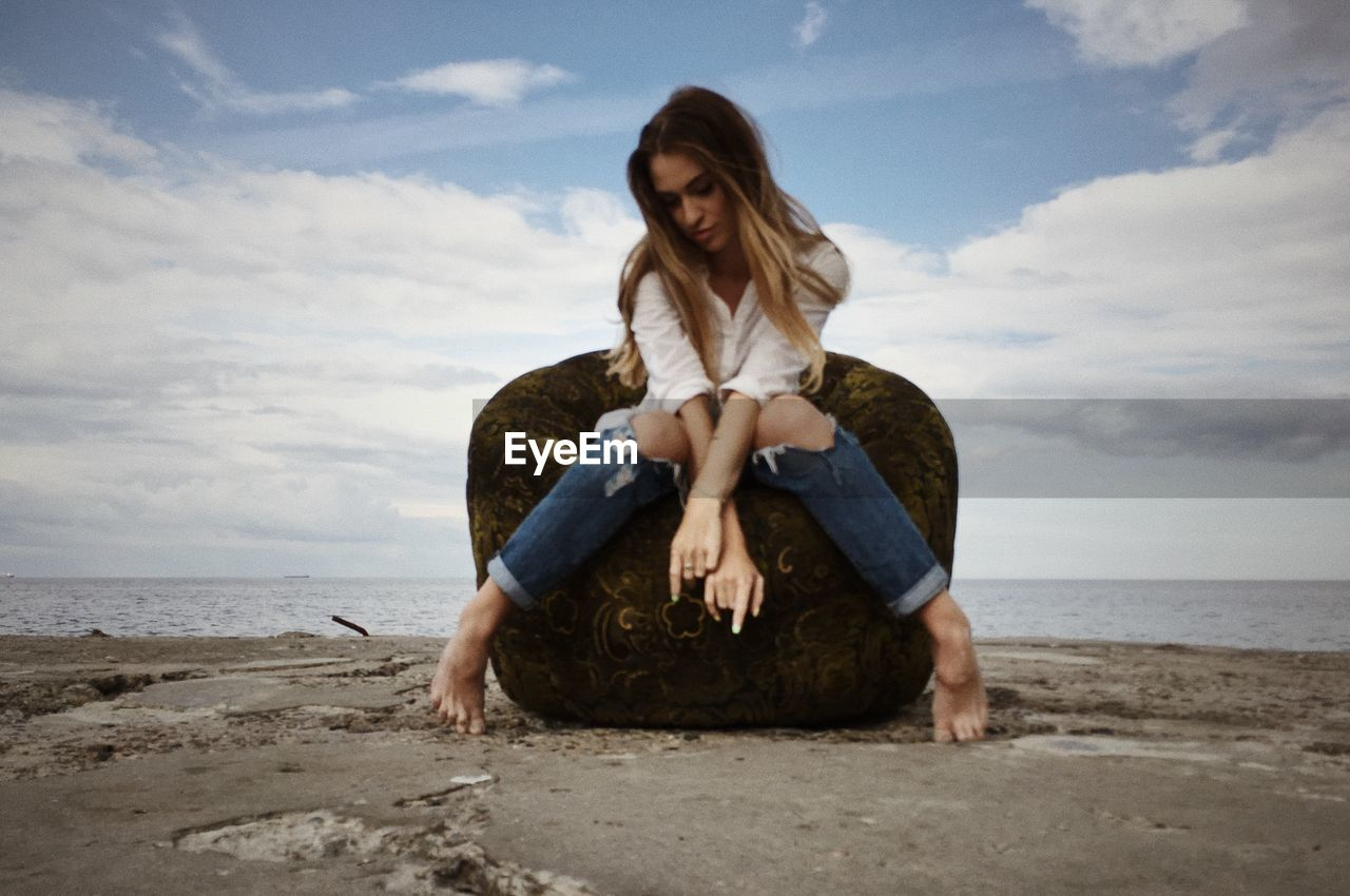 Young woman sitting on chair by sea against cloudy sky