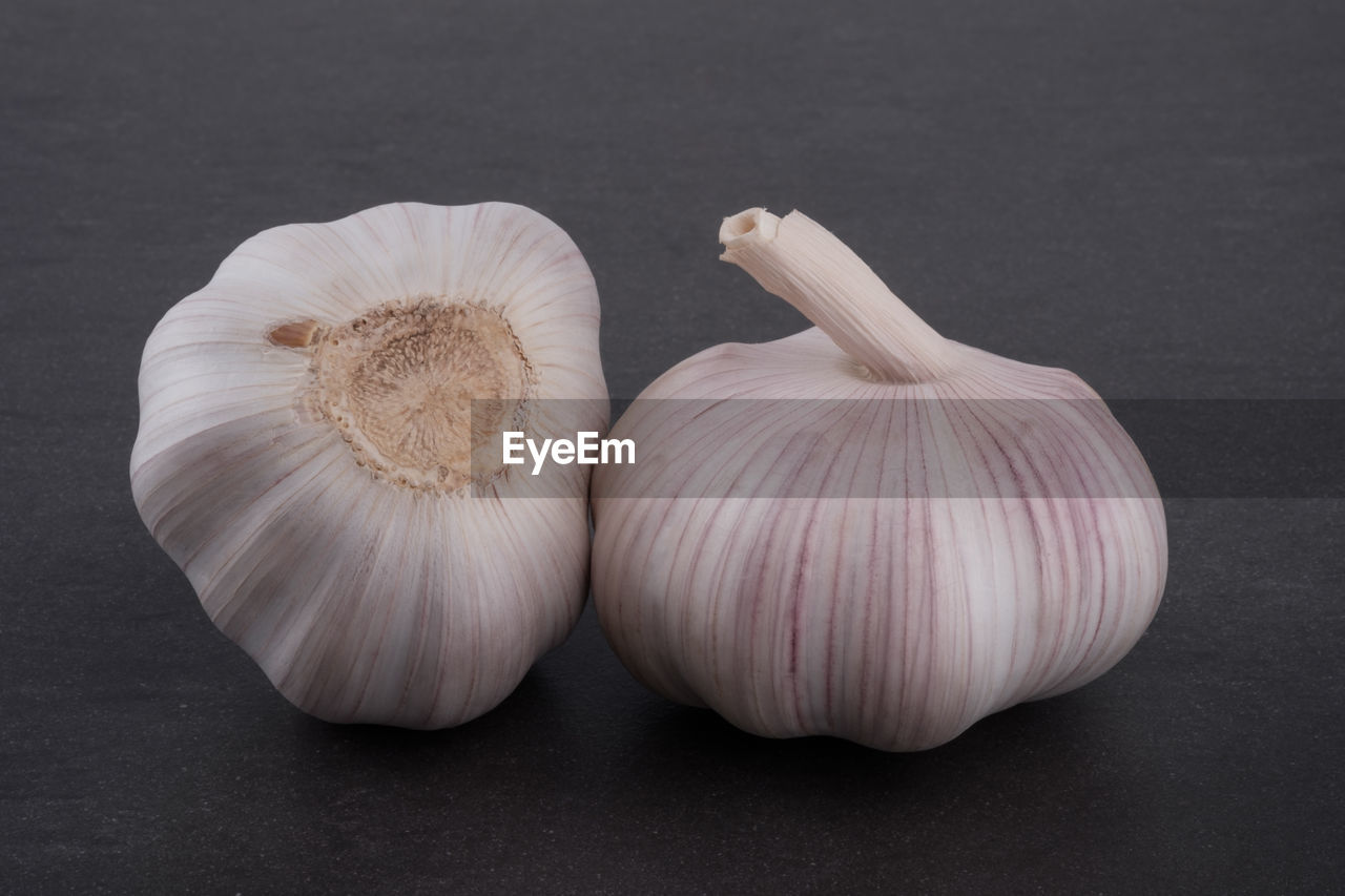 food and drink, garlic, food, freshness, still life, spice, garlic bulb, studio shot, ingredient, close-up, indoors, vegetable, raw food, no people, wellbeing, healthy eating, white color, table, group of objects, onion, black background, garlic clove