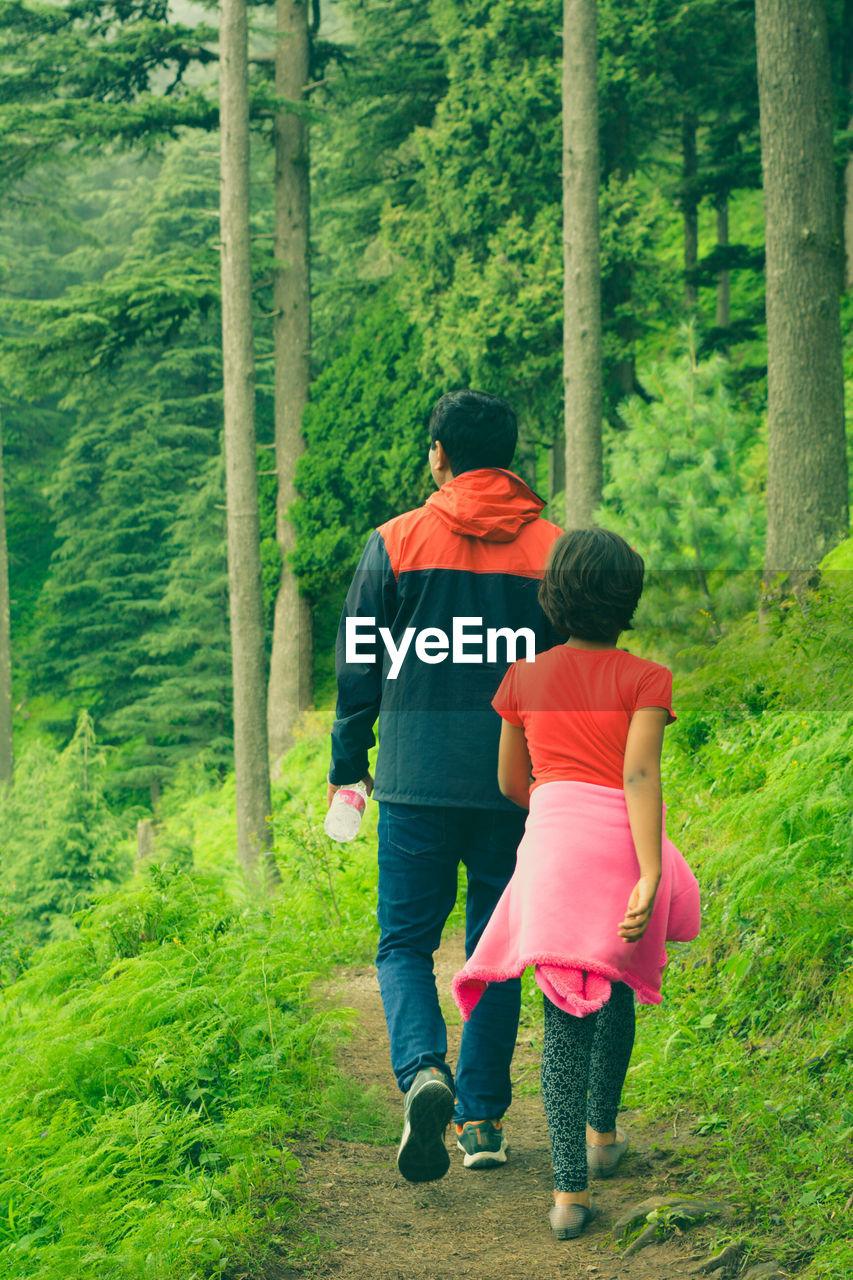 rear view, walking, two people, togetherness, full length, real people, nature, holding hands, casual clothing, tree, green color, day, love, leisure activity, growth, childhood, bonding, lifestyles, grass, outdoors, beauty in nature, men, women, people