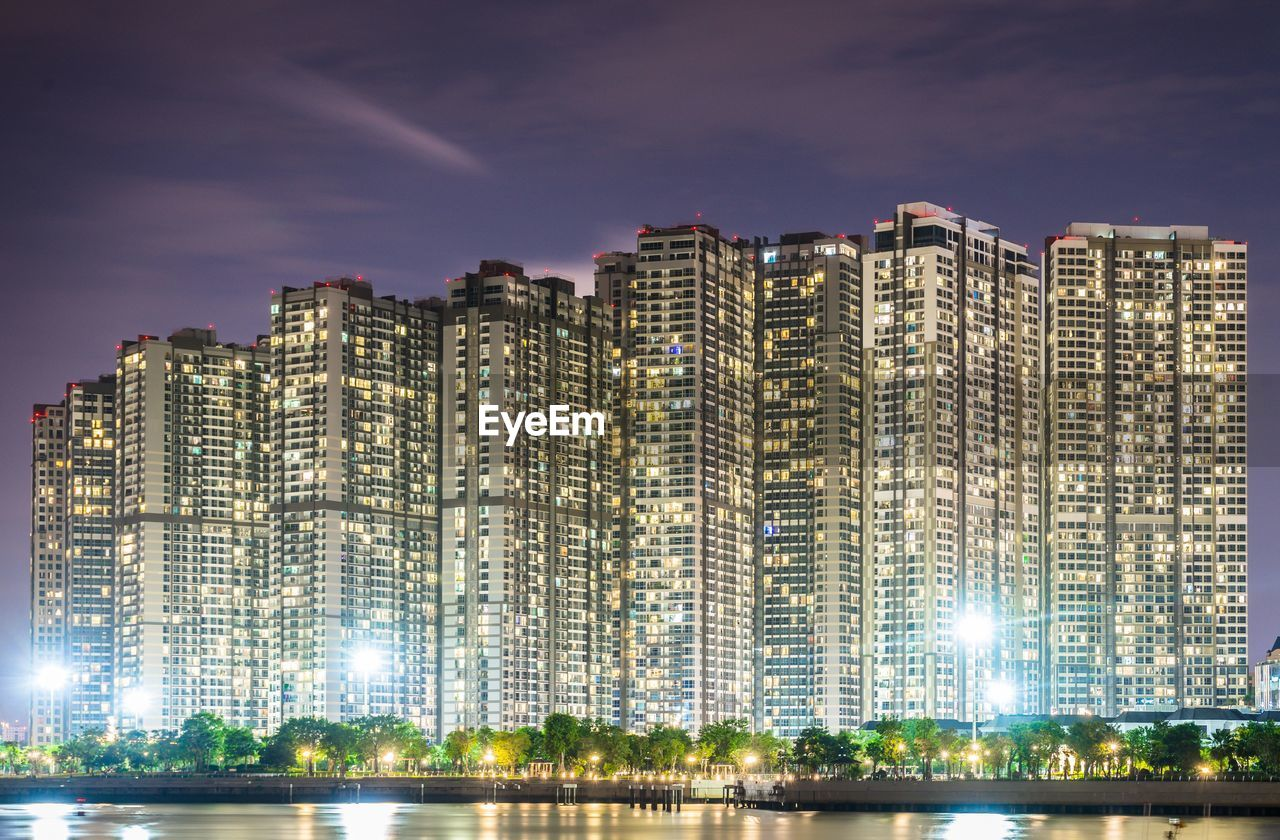 building exterior, built structure, architecture, sky, city, building, illuminated, night, no people, nature, cloud - sky, residential district, cityscape, water, outdoors, office building exterior, skyscraper, waterfront, modern, apartment