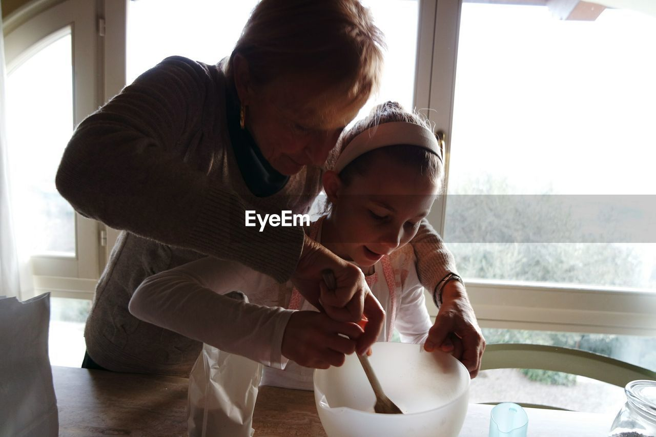 Mother Teaching Daughter To Mix Batter In Bowl At Table Against Window