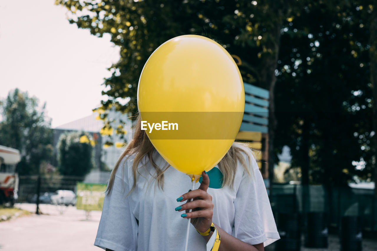 Woman Holding Yellow Balloon In Front Of Face Against Trees