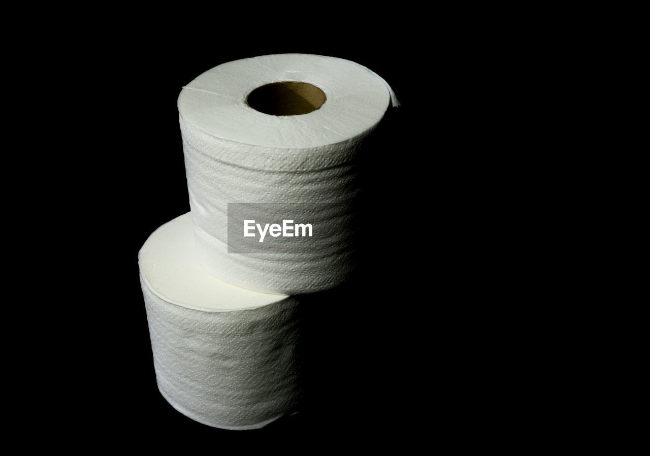 rolled up, spool, black background, toilet paper, studio shot, sewing item, no people, close-up, indoors