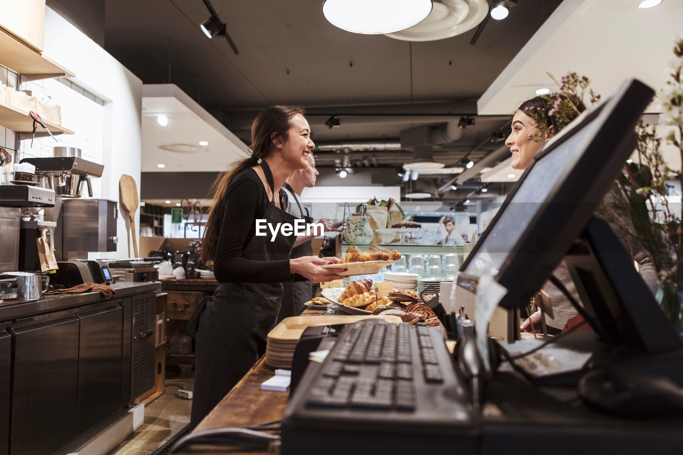 Saleswoman serving food to customer at cafe