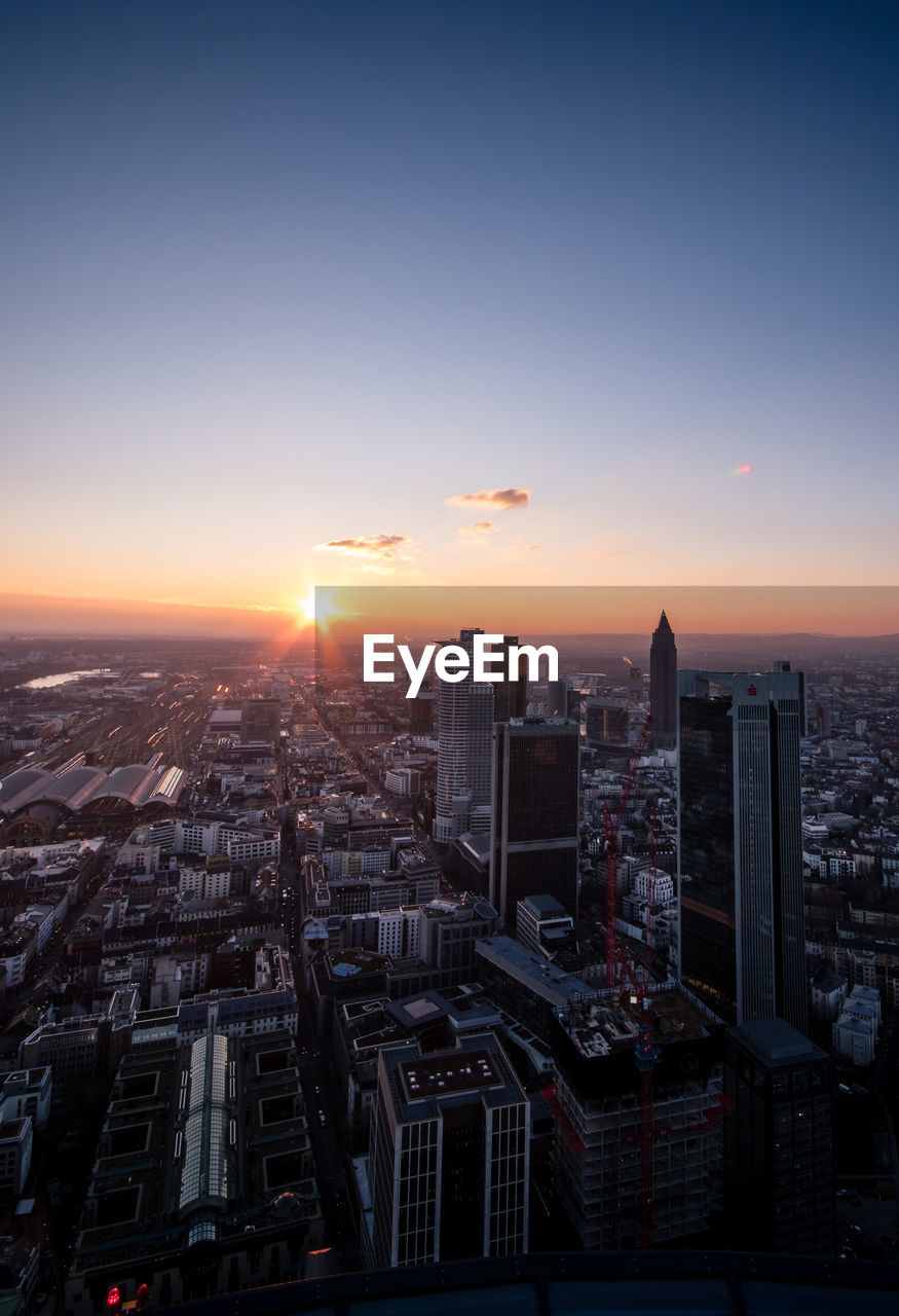 sky, building exterior, city, architecture, built structure, sunset, cityscape, building, crowd, office building exterior, sun, crowded, skyscraper, nature, residential district, sunlight, high angle view, urban skyline, tall - high, outdoors, modern, financial district, settlement