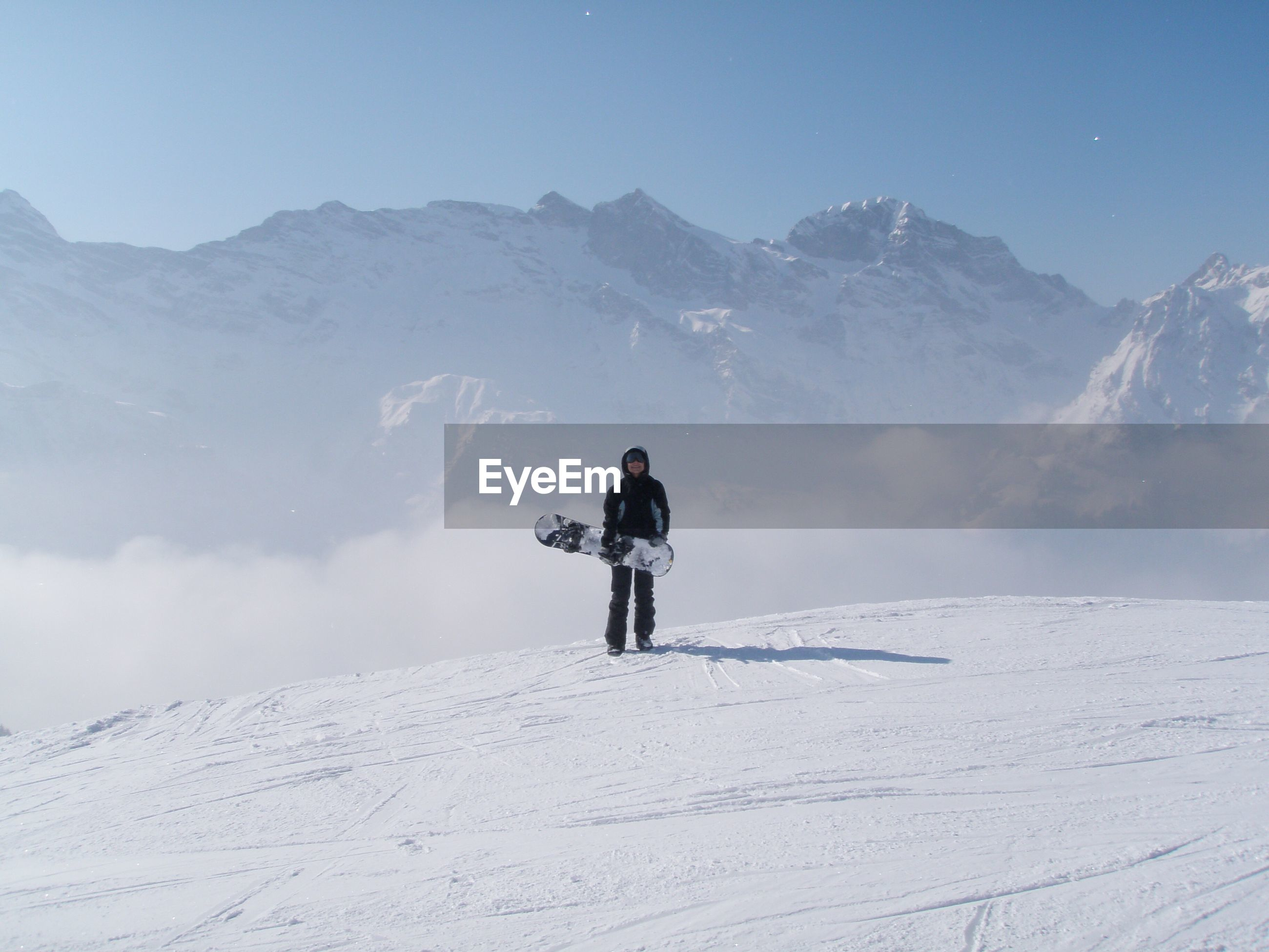 Snowboarder standing against snowcapped mountains