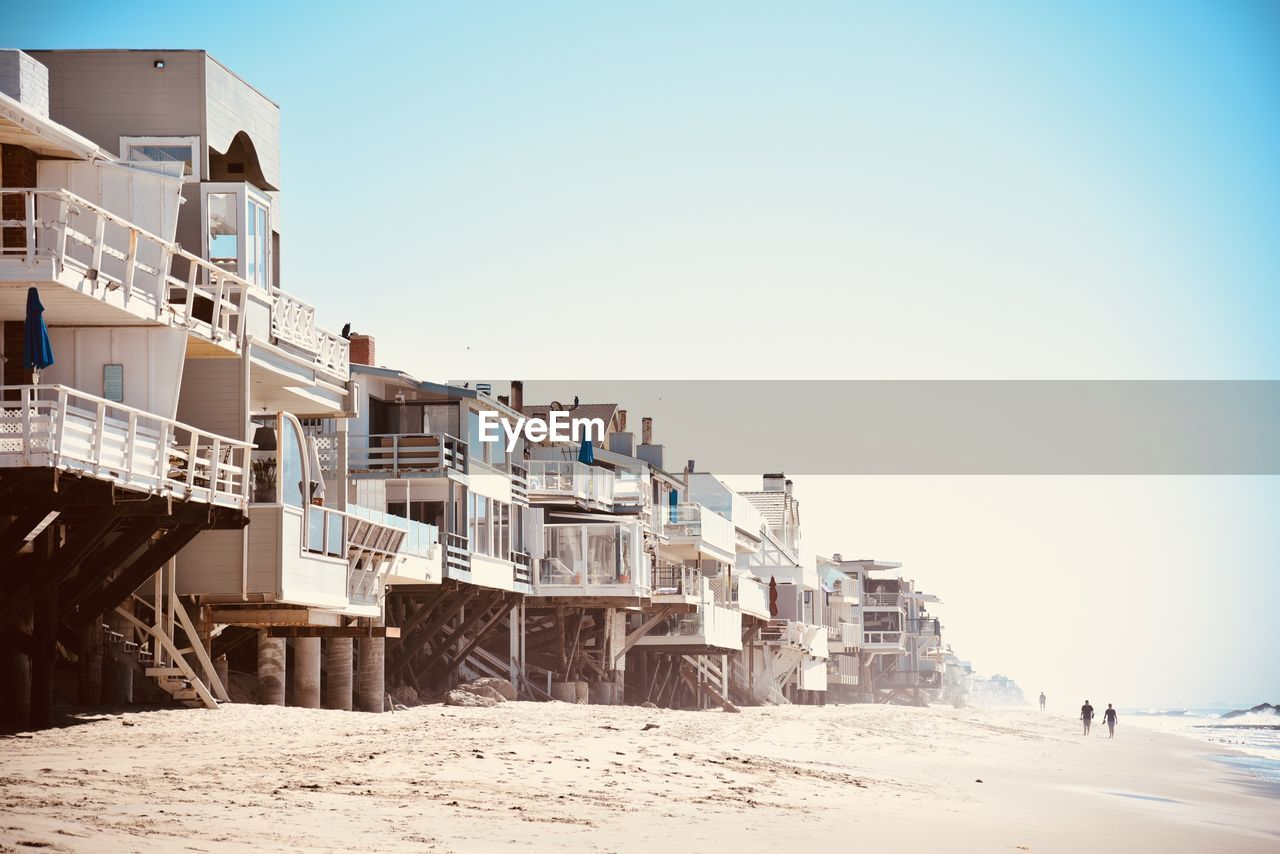 sky, built structure, building exterior, architecture, clear sky, nature, copy space, day, land, incidental people, building, residential district, cold temperature, snow, winter, outdoors, sunlight, city, beach, apartment