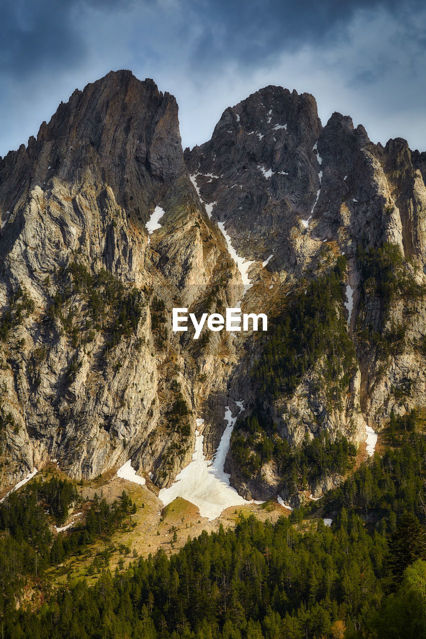 mountain, scenics - nature, beauty in nature, sky, rock, nature, mountain range, rock - object, tranquil scene, non-urban scene, cloud - sky, solid, tranquility, environment, day, no people, water, rock formation, plant, geology, outdoors, formation, mountain peak, flowing water, flowing