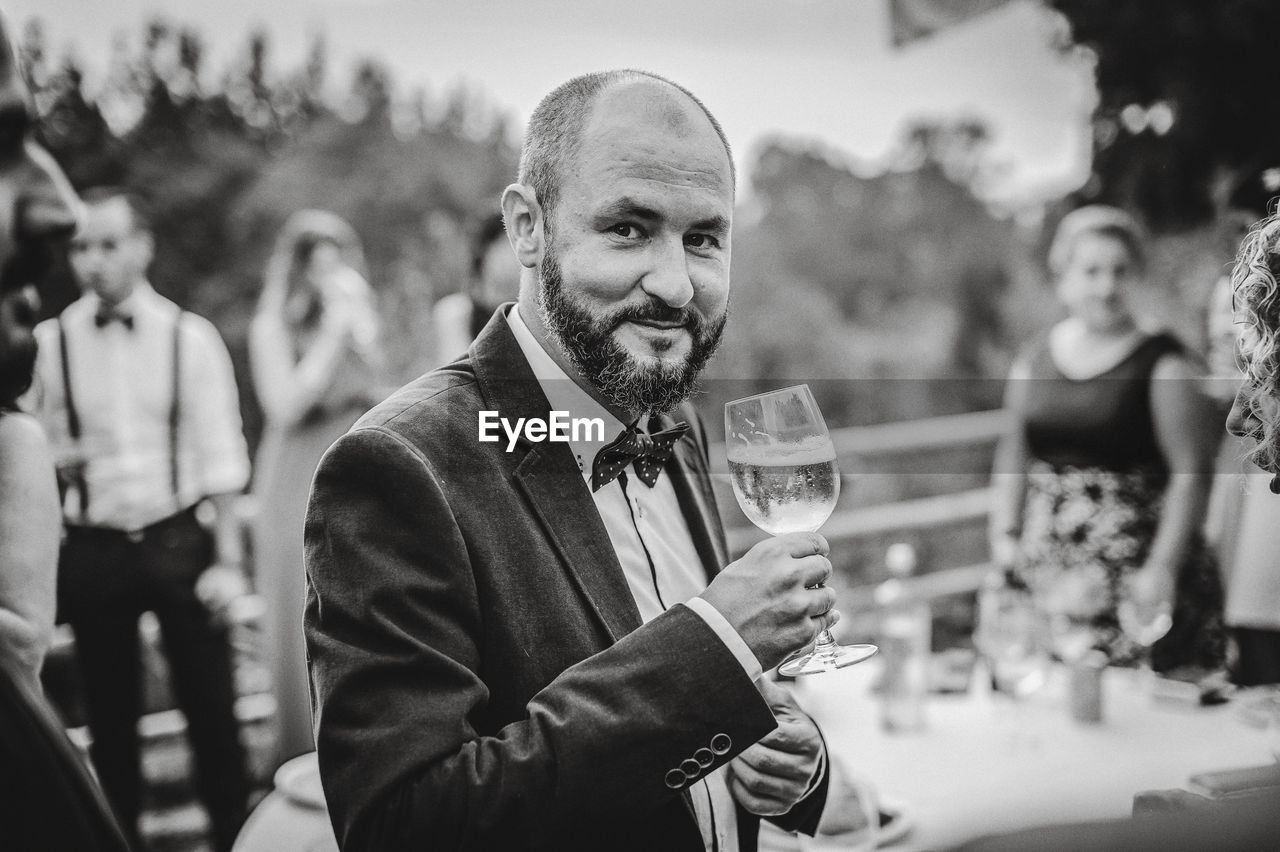 Portrait Of Smiling Man Holding Alcoholic Drink During Party