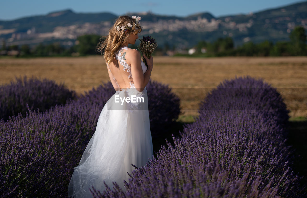 Bride Holding Flowers While Standing Amidst Plants On Field