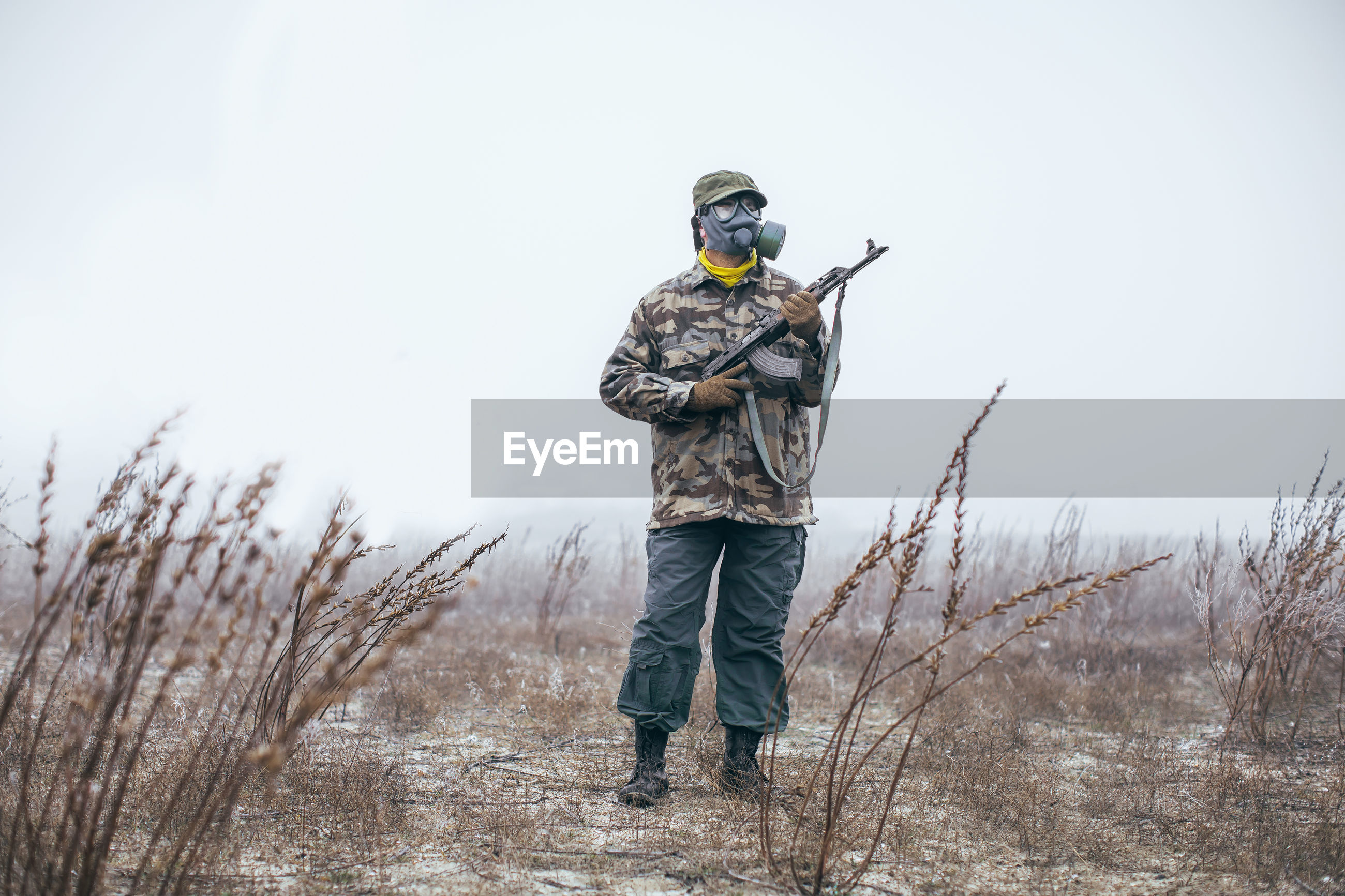 Full length of soldier with gun standing on field