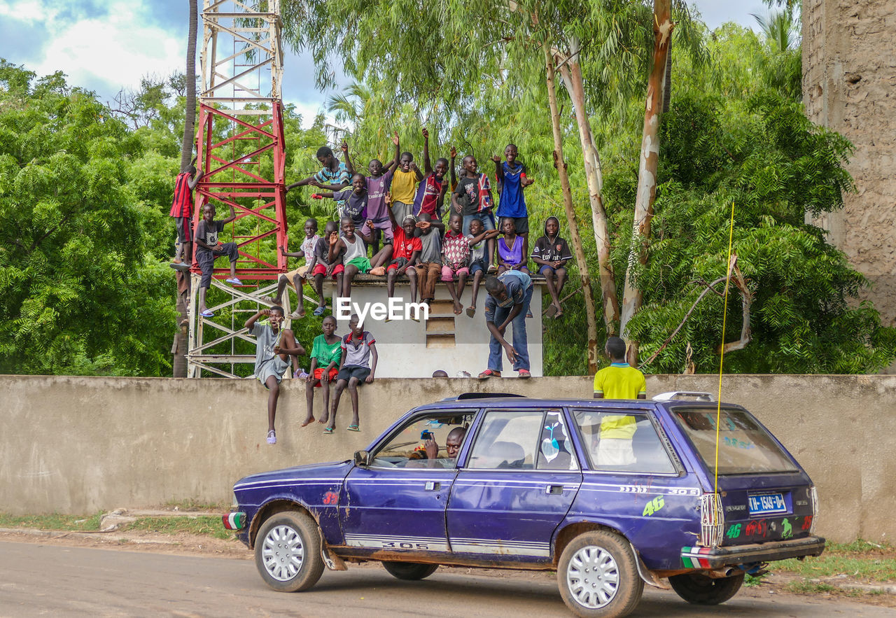 transportation, tree, group of people, mode of transportation, real people, day, plant, nature, car, men, motor vehicle, women, people, travel, land vehicle, leisure activity, outdoors, medium group of people, adult, crowd